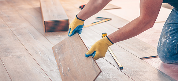 A worker installing light brown wood flooring
